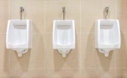 Modern interior design of white ceramic urinals Stock Images
