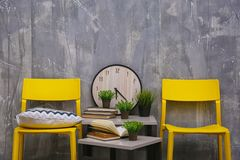 Modern interior design with yellow chairs and little table. On grey background royalty free stock photo