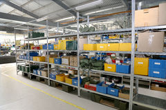 Modern factory warehouse on mechanical modern plant, colorful plastic packaging boxes, personal protection on metal racks. Modern interior electronics components royalty free stock photos