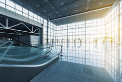 Modern interior. Escalator in lobby of modern office building, glass walls and reflective floor, natural light and flare Royalty Free Stock Images