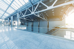 Modern interior. Escalators and corridors of modern office building or airport, glass walls and reflective floor, natural light and flare Royalty Free Stock Photos