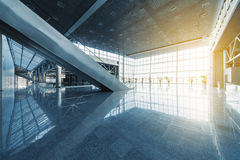 Modern interior. Escalators and corridors of modern office building or airport, glass walls and reflective floor, natural light and flare Royalty Free Stock Photo