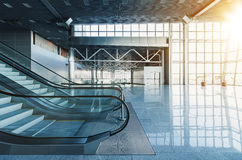 Modern interior. Escalators and stairs in lobby of modern office building, airport or shopping mall, glass walls and reflective floor, natural light and flare Royalty Free Stock Photos