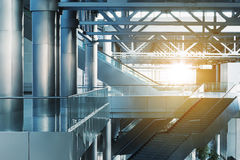 Modern interior. Escalators and stairs in  modern office building, airport or transport terminal, glass walls and reflective floor; natural light and flare Royalty Free Stock Images