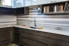 Modern interior kitchen design with brown base cabinets and white wall cabinets. Small kitchen area with counter top and backsplash. Kitchen room has brown Stock Photos