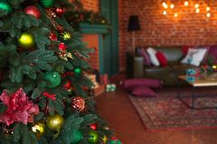 Modern interior of living room. Creative Christmas tree, contemporary fireplace and large olive sofa in loft interior royalty free stock image