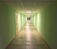 Modern interior in office building. Long empty hall with distant doors and office entrance. Royalty Free Stock Images