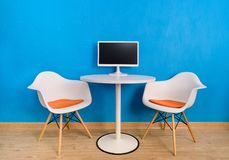 Modern interior office table and two chairs with computer monitor. Modern interior round table with computer monitor atop and two white chairs near blue wall stock photos
