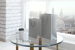 Modern interior with shopping bag. Empty shopping bag, coffee cup and smartphone placed on glass table in modern brick interior with city view and daylight. Mock Stock Photos
