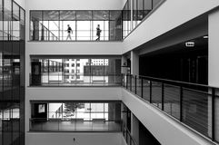 Modern interior and two people walking. Modern public building interior with two figures walking in the background. High contrast black and white picture Stock Photography