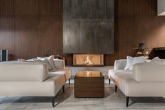 Modern interior with wooden wall and burning fireplace stock photography