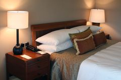 Modern Interiors - Bedrooms. Nice bedroom with a modern style, Bed, two lamps and lots of pillows Stock Photography