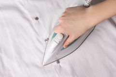Modern iron in female hand ironing cotton shirt Royalty Free Stock Photography