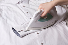 Modern iron in female hand ironing sleeve of cotton shirt Stock Photos