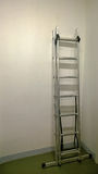 Modern iron ladder leaning against a white wall in the assembled condition during repair in apartment or office Royalty Free Stock Images