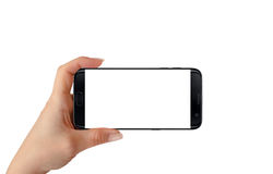 Modern isolated black smart phone in woman hand in horizontal position. Stock Photography