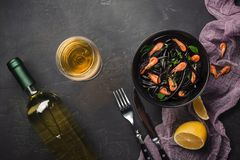Modern italian dinner, Mediterranean food, black cuttlefish ink spaghetti pasta with seafood, olive oil and basil, on dark rusty. Table. White wine on copy stock photo