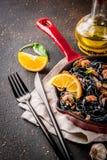 Black cuttlefish ink pasta with seafood. Modern italian dinner, Mediterranean food, black cuttlefish ink spaghetti pasta with seafood, olive oil and basil,  on Stock Photography