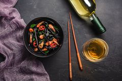 Modern japanese dinner, Mediterranean food, black cuttlefish ink spaghetti pasta with seafood, olive oil and basil, on dark rusty. Table. White wine on copy royalty free stock images