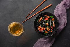 Modern japanese dinner, Mediterranean food, black cuttlefish ink spaghetti pasta with seafood, olive oil and basil, on dark rusty. Table. White wine on copy royalty free stock image
