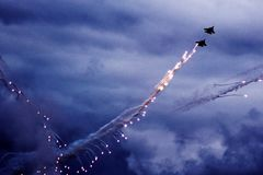 Modern jet fighter is firing a set of flares on the blue sky. Cloud condensation on the wings. royalty free stock photo