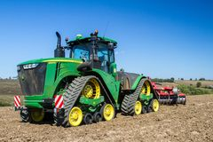 Modern john deere caterpilla tractor cultivating English crop field Stock Image