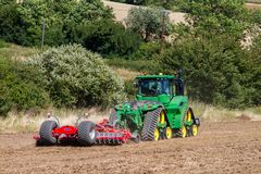 Modern john deere caterpilla tractor cultivating English crop field Stock Image