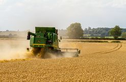 Modern John Deere combine harvester cutting crops Stock Photos