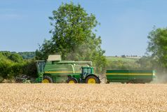 Modern John Deere combine harvester cutting crops with tractor and trailer Royalty Free Stock Photography