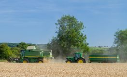 Modern John Deere combine harvester cutting crops with tractor and trailer Royalty Free Stock Photo