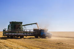 Modern John Deere combine harvesting grain on a storage trailer Royalty Free Stock Images