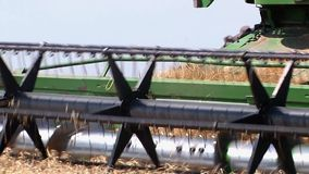Modern John Deere combine harvesting grain on a storage trailer stock footage