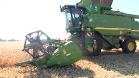 Modern John Deere combine harvesting grain on a storage trailer stock video footage