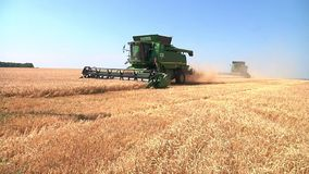 Modern John Deere combine harvesting grain on a storage trailer stock video