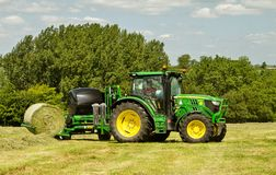 Modern John Deere green tractor with round bale wrapper Stock Photo