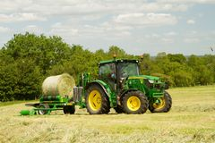 Modern John Deere green tractor with round bale wrapper Royalty Free Stock Photo