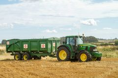 Modern John Deere tractor pulling green trailer. With crops corn wheat barley working golden stubble field Stock Images