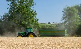 Modern John Deere tractor pulling green trailer Royalty Free Stock Photo