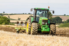 Modern John Deere tractor pulling a plough royalty free stock images