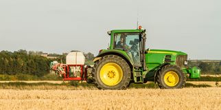 Modern john deere tractor Tractor spraying field stubble crops Stock Photography