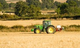 Modern john deere tractor Tractor spraying field stubble crops Royalty Free Stock Images