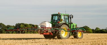 Modern john deere tractor Tractor spraying field stubble crops Royalty Free Stock Image