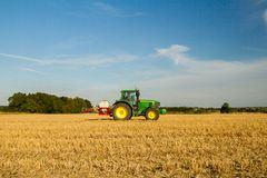 Modern john deere tractor Tractor spraying field stubble crops Royalty Free Stock Photo