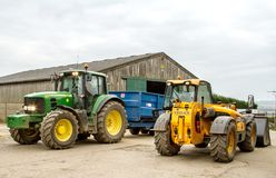 Modern John Deere tractor and trailer parked with jcb loader Royalty Free Stock Photos