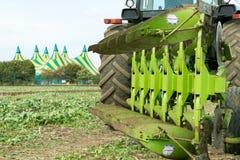 Modern John Deere traktor som drar en plöja Arkivfoto