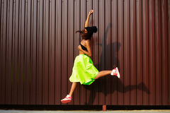 Modern jumping young stylish woman in bright modern cloth Stock Photos