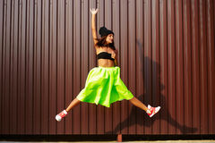Modern jumping young stylish woman in bright modern cloth Royalty Free Stock Photos