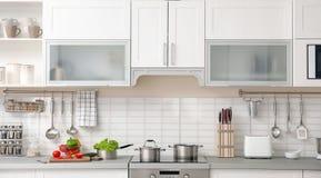 Modern kökinre med housewaren och möblemang arkivbilder