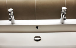 Modern kerrock sink with two shining tap faucets Royalty Free Stock Photography
