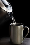 Modern kettle pouring water into cup isolated on black Stock Images